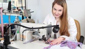 Mujer de la costurera que cose en una tienda de los sastres Foto de archivo