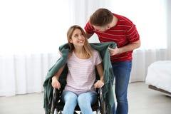 Mujer de la cubierta del hombre en silla de ruedas con la tela escocesa en casa fotografía de archivo libre de regalías