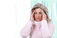 Mujer de la Edad Media con dolor de cabeza y jaqueca Fotos de archivo libres de regalías
