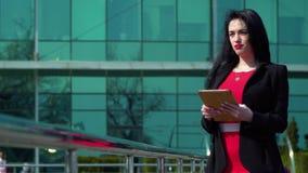 Mujer de la elegancia con la tableta digital en el fondo del centro de negocios almacen de video