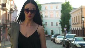 Mujer de la elegancia en ropa de moda y gafas de sol que camina en la cámara lenta almacen de metraje de vídeo