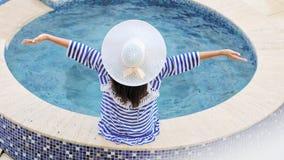 Mujer de la elegancia de la vista posterior del alto ángulo en sombrero con el arco que se sienta en el borde de la piscina o del metrajes