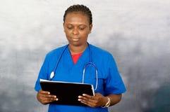 Mujer de la enfermera que sostiene un cuaderno imágenes de archivo libres de regalías