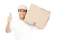 Mujer de la entrega que lleva un paquete y que muestra los pulgares para arriba Imagen de archivo libre de regalías