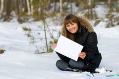 Mujer de la escritura en bosque del invierno Imagenes de archivo