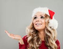 Mujer de la feliz Navidad en el espacio de Santa Hat Showing Empty Copy Imagenes de archivo