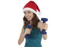 Mujer de la feliz Navidad que se resuelve con pesas de gimnasia Imágenes de archivo libres de regalías
