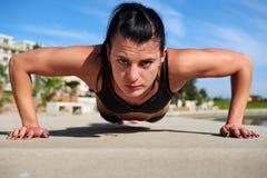Mujer de la flexión de brazos Imagen de archivo libre de regalías