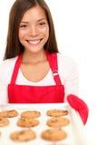 Mujer de la hornada que muestra las galletas Fotos de archivo