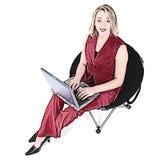 Mujer de la ilustración en rojo con la computadora portátil en silla negra Foto de archivo