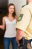Mujer de la interrogación del oficial de policía en la puerta principal Fotografía de archivo libre de regalías