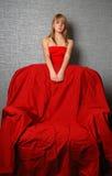Mujer de la juventud en butaca roja y grande Foto de archivo