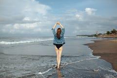 Mujer de la libertad y de la felicidad que camina en la playa, gozando del océano durante viaje imagen de archivo