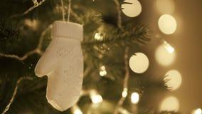 Mujer de la mano que adorna en el árbol de navidad con las luces del resplandor de la Navidad metrajes