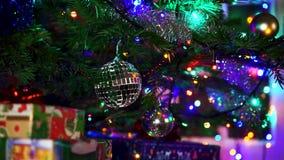 Mujer de la mano que adorna en el árbol de navidad con las luces del resplandor de la Navidad almacen de metraje de vídeo