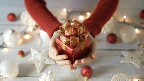 Mujer de la mano que sostiene la caja de regalo roja con la decoración de la Navidad en de madera blanco almacen de metraje de vídeo