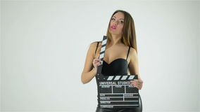 Mujer de la moda con los labios rojos atractivos que llevan a cabo palmada del cine aislada en el fondo blanco Tiro estupendo del almacen de video