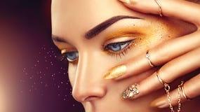 Mujer de la moda de la belleza con maquillaje de oro imágenes de archivo libres de regalías