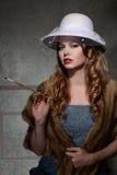 mujer de la moda de los años 40 con el cigarrillo Fotografía de archivo libre de regalías