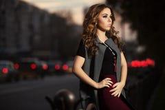 Mujer de la moda de los jóvenes con los pelos rizados largos en la calle de la ciudad de la noche Imágenes de archivo libres de regalías
