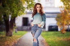 Mujer de la moda de los jóvenes con los pelos rizados largos que camina en la calle de la ciudad Imagen de archivo