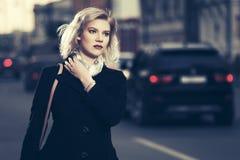 Mujer de la moda de los jóvenes en capa negra que camina en la calle de la ciudad Fotografía de archivo