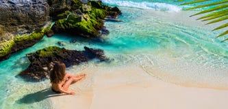 Mujer de la moda de los jóvenes en el bikini que se sienta en la playa tropical Beautif Fotos de archivo