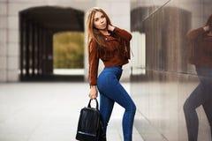 Mujer de la moda de los jóvenes en la chaqueta de cuero con el bolso imagenes de archivo