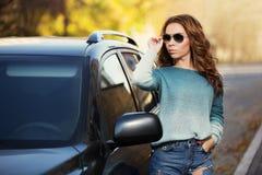 Mujer de la moda de los jóvenes en las gafas de sol que se colocan al lado del coche al aire libre imagenes de archivo
