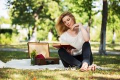 Mujer de la moda de los jóvenes que lee un libro en el parque Fotografía de archivo