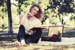Mujer de la moda de los jóvenes que lee un libro en parque de la ciudad Fotografía de archivo