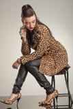 Mujer de la moda de los jóvenes que mira abajo mientras que se sienta Fotografía de archivo