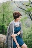 Mujer de la moda de los jóvenes que se sienta en una piedra con Mountain View hermoso detrás Imagen de archivo libre de regalías