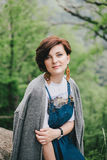 Mujer de la moda de los jóvenes que se sienta en una piedra con Mountain View hermoso detrás Foto de archivo