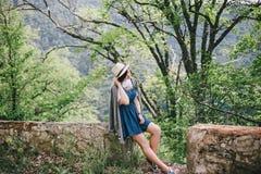 Mujer de la moda de los jóvenes que se sienta en una piedra con Mountain View hermoso detrás Imágenes de archivo libres de regalías