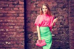 Mujer de la moda del encanto en la pared de ladrillo vieja Foto de archivo