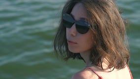 Mujer de la moda en gafas de sol con la reflexión de la playa almacen de video