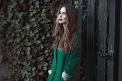 Mujer de la moda en la capa verde que presenta al aire libre Imagen de archivo