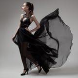 Mujer de la moda en vestido negro que agita Fondo gris Foto de archivo