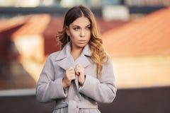 Mujer de la moda de los jóvenes en capa gris clara que camina en calle de la ciudad imagen de archivo libre de regalías