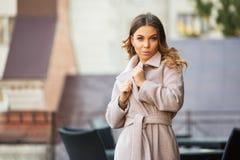 Mujer de la moda de los jóvenes en pálido - capa rosada que camina en calle de la ciudad imagen de archivo libre de regalías