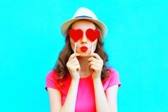 Mujer de la moda que hace un beso que oculta forma roja de la piruleta de un corazón ella ojos sobre azul colorido Fotografía de archivo