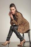 Mujer de la moda que juega con su pendiente Foto de archivo