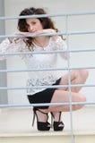 Mujer de la moda que se inclina contra una verja del hierro Fotografía de archivo