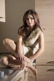 Mujer de la moda que se sienta en cocina Imagen de archivo