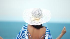 Mujer de la moda de la vista posterior en el sombrero blanco con el mar de admiración trasero atractivo desnudo que aumenta la ma almacen de video