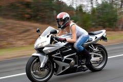 Mujer de la motocicleta que apresura Fotografía de archivo libre de regalías