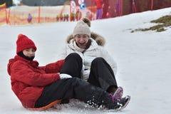 Mujer de la muchacha de la familia sledding en la nieve de la colina del invierno Fotografía de archivo