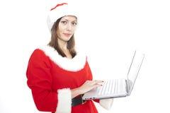 Mujer de la Navidad con la computadora portátil Fotos de archivo