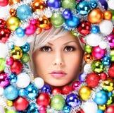 Mujer de la Navidad con las bolas coloreadas. Cara de la muchacha hermosa Imagen de archivo